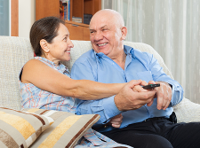 Couple laughing and watching television together